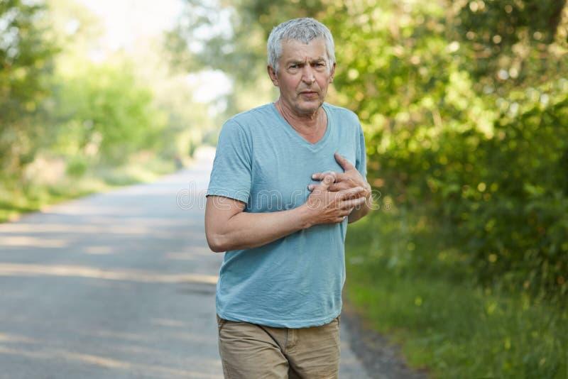 La foto del hombre maduro del cansancio siente dolor en corazón después de activar, tiene expresión hosca, lleva la ropa casual,  fotografía de archivo