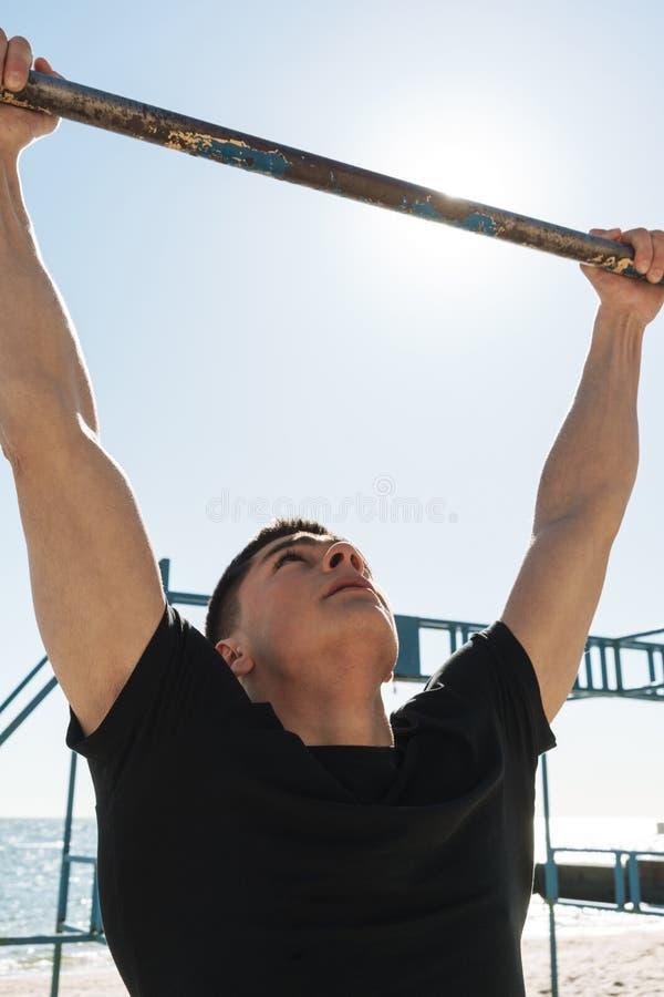 La foto del hombre muscular que hace tirón sube en barra gimnástica horizontal durante entrenamiento de la mañana por la playa imagen de archivo