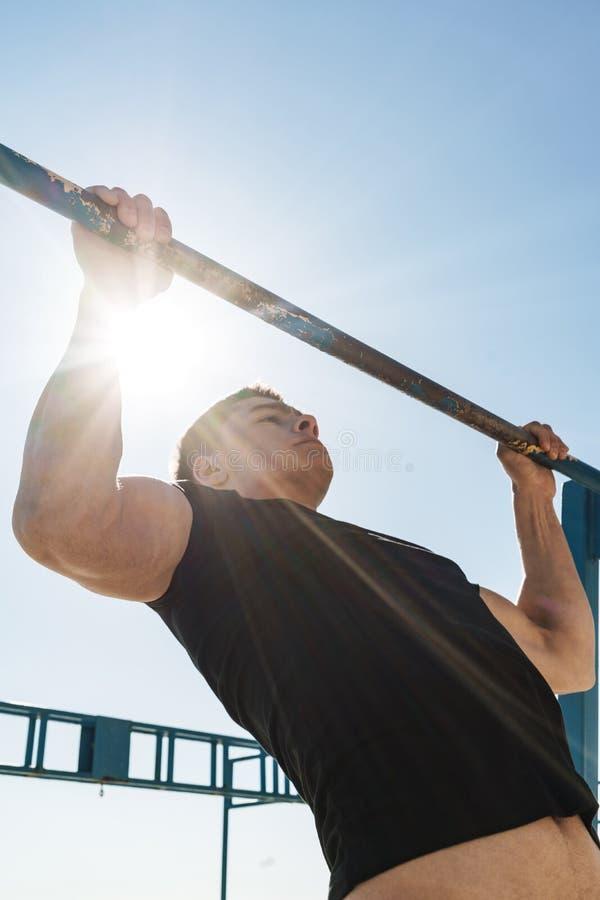 La foto del individuo masculino que hace tirón sube en barra gimnástica horizontal durante entrenamiento de la mañana por la play fotos de archivo