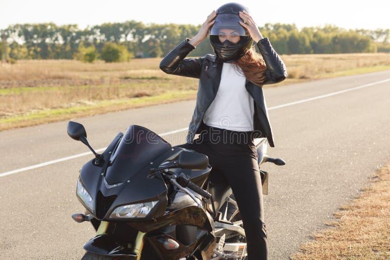 La foto del motorista femenino atractivo vestido en la chaqueta de cuero, lleva el casco, presenta en la moto contra fondo del ca foto de archivo libre de regalías