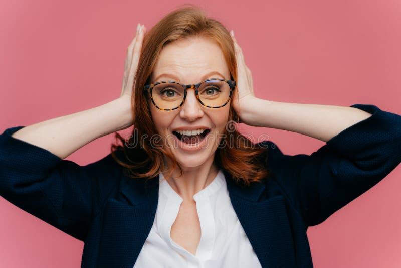 La foto del oficinista de sexo femenino del pelirrojo positivo guarda las palmas en los oídos, mira feliz la cámara, lleva el equ fotografía de archivo