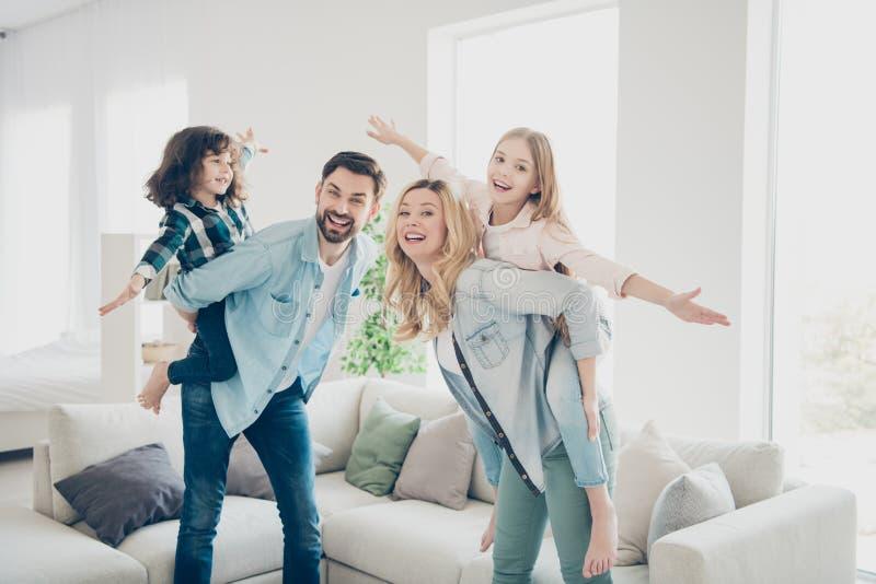 La foto del perfil de cuatro miembros de la familia que tienen mejor tiempo libre finge los apartamentos del aeroplano del vuelo  foto de archivo libre de regalías