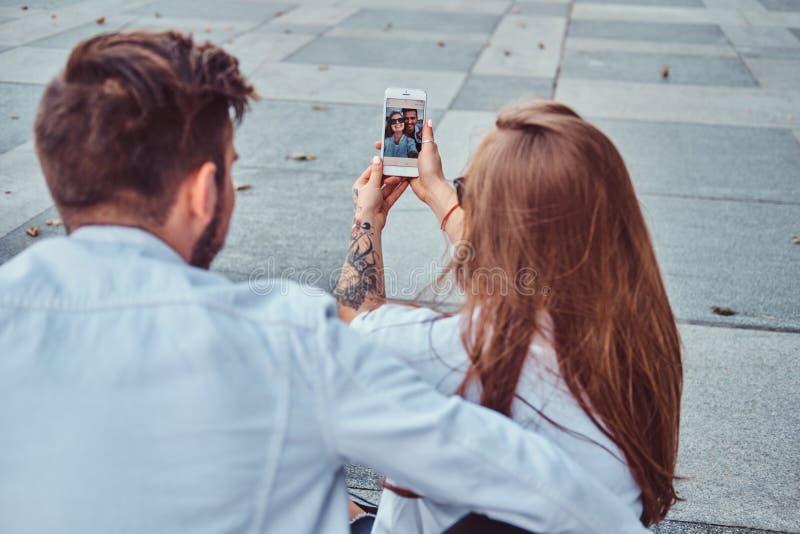 La foto del primer de un par feliz joven hace el selfie junto al aire libre imagenes de archivo