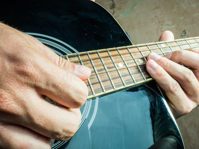 La foto del primer de una guitarra acústica jugó por a foto de archivo libre de regalías