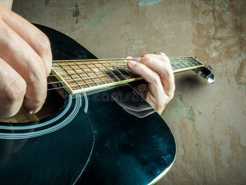 La foto del primer de una guitarra acústica jugó por a fotos de archivo