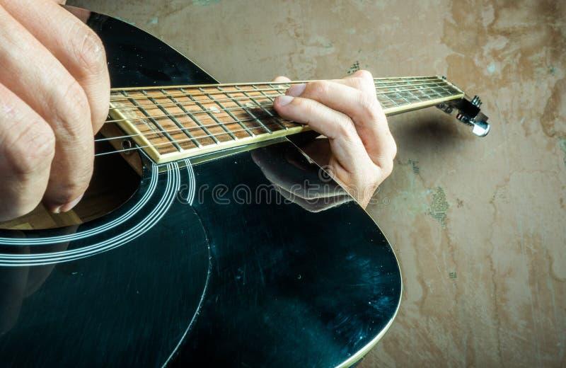 La foto del primer de una guitarra acústica jugó por a imagen de archivo