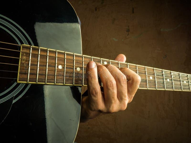 La foto del primer de una guitarra acústica jugó por a fotografía de archivo