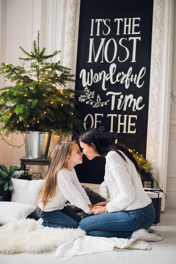 La foto del primo piano della bambina in maglione tricottato bacia sua madre mentre si siede sul sofà al Natale immagini stock
