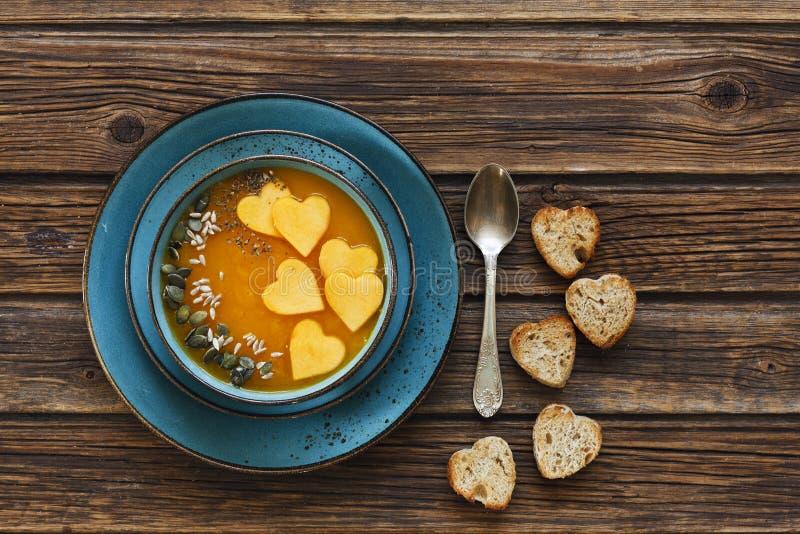 La foto del primo piano del piatto con la minestra casalinga fresca della crema della zucca con i semi ed il cuore modellano i pa fotografia stock