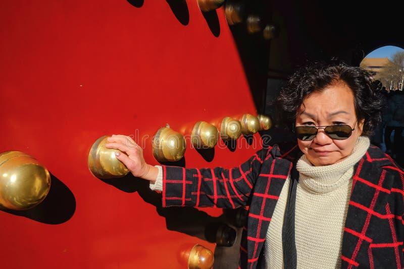 La foto del ritratto delle donne asiatiche senior prende il portone severo del palazzo a Pechino immagine stock libera da diritti