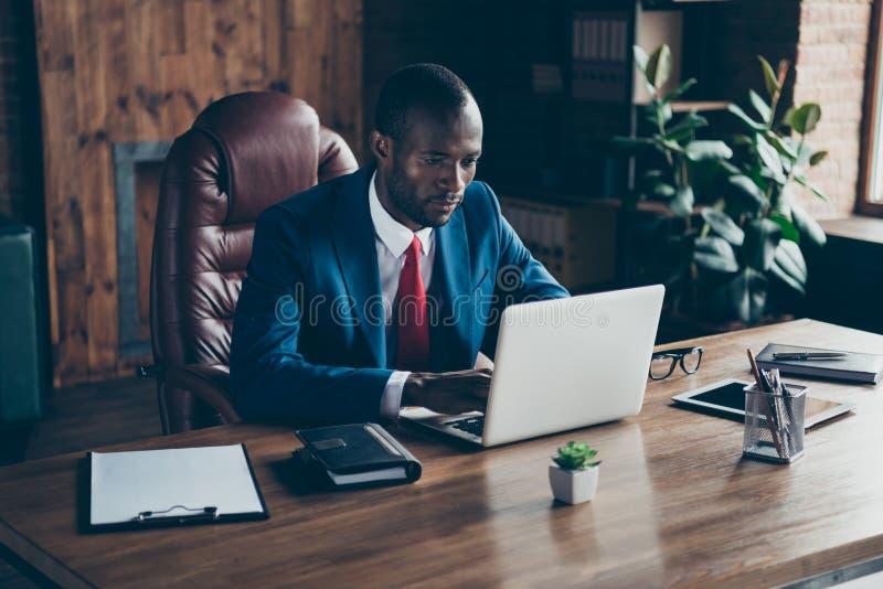 La foto del taccuino mandante un sms del tipo scuro della pelle con i partner indossa la sedia di seduta dell'ufficio del costume fotografie stock libere da diritti