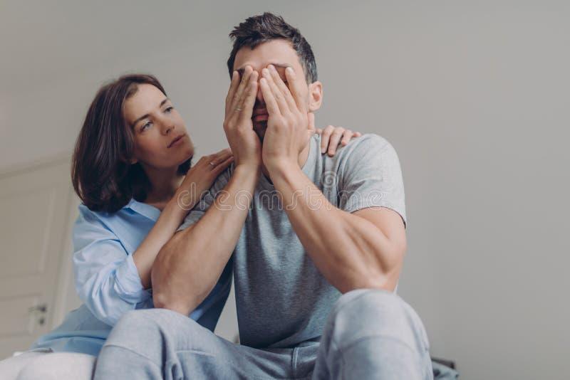 La foto del varón deprimido vestida ocasional, su mujer hermosa lo conforta, se sienta junta en dormitorio, tiene problemas en vi imágenes de archivo libres de regalías