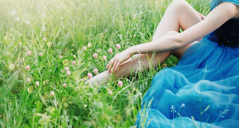 La foto delicada encantadora del arte con colores creativos, la se?ora toca los fingeres de la mano de sus piernas desnudas atrac fotografía de archivo