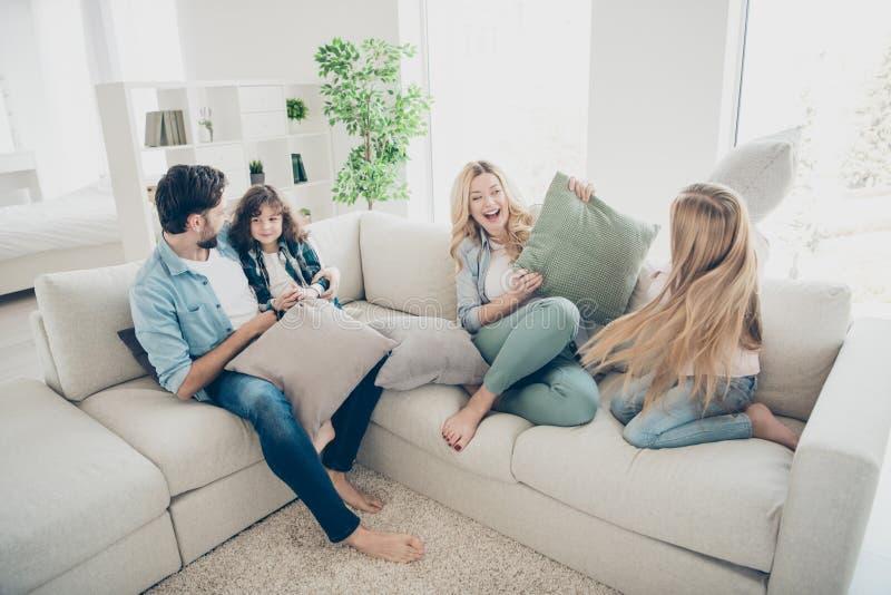 La foto dell'angolo alto di grandi membri della famiglia quattro passa il tempo libero che lega giocando i cuscini si siede lo st fotografia stock