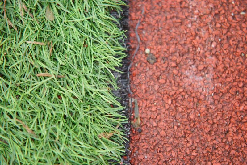 La foto dell'atletica artificiale del primo piano con erba verde si è combinata con erba artificiale immagine stock