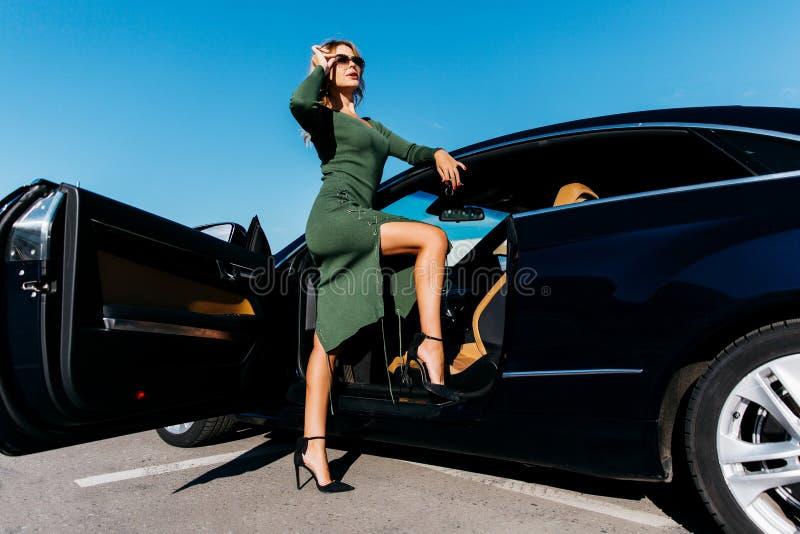La foto della bionda con digita gli occhiali da sole nella condizione lunga del vestito vicino all'automobile nera con la porta a immagini stock