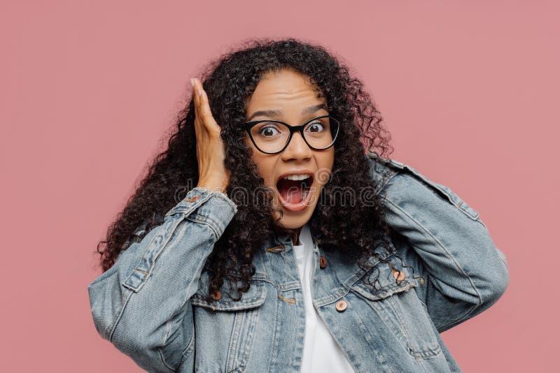 La foto della donna afroamericana sorpresa copre le orecchie, urla fortemente, trascura il suono rumoroso, tiene la bocca ampiame fotografia stock