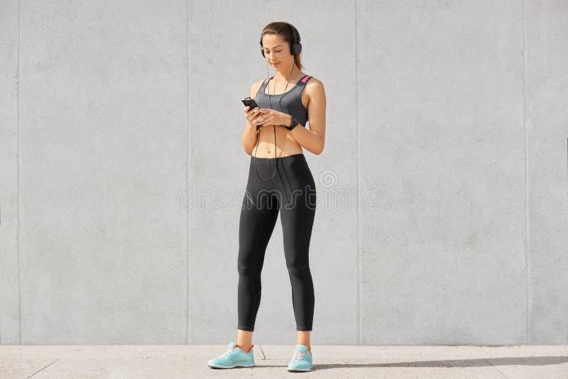 La foto della donna atheltic sportiva seria tiene il telefono cellulare moderno, ascolta musica con le cuffie, indossa lo smartwa fotografia stock
