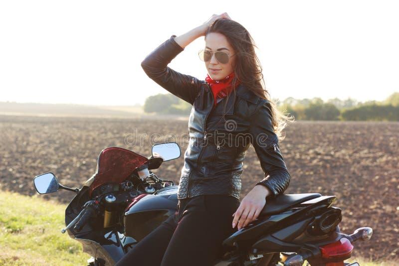 La foto della donna atrractive indossa le tonalità d'avanguardia, bomber, tiene la mano sulla testa, pose vicino a motorrbike, go immagini stock