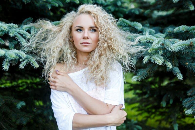 La foto della donna dai capelli lunghi riccia accanto ad abete si ramifica fotografia stock
