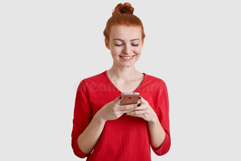 La foto della donna dai capelli rossi soddisfatta con pelle freckled, tiene il telefono cellulare moderno, invia il messaggio di  fotografia stock libera da diritti