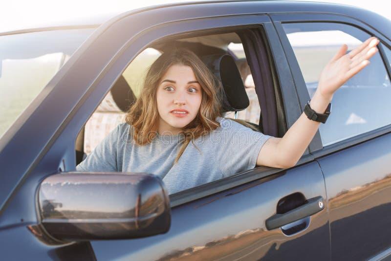 La foto della donna imbarazzata gestures sebbene finestra di automobile, essendo infastidendo per aspettare lungamente e per star fotografia stock libera da diritti