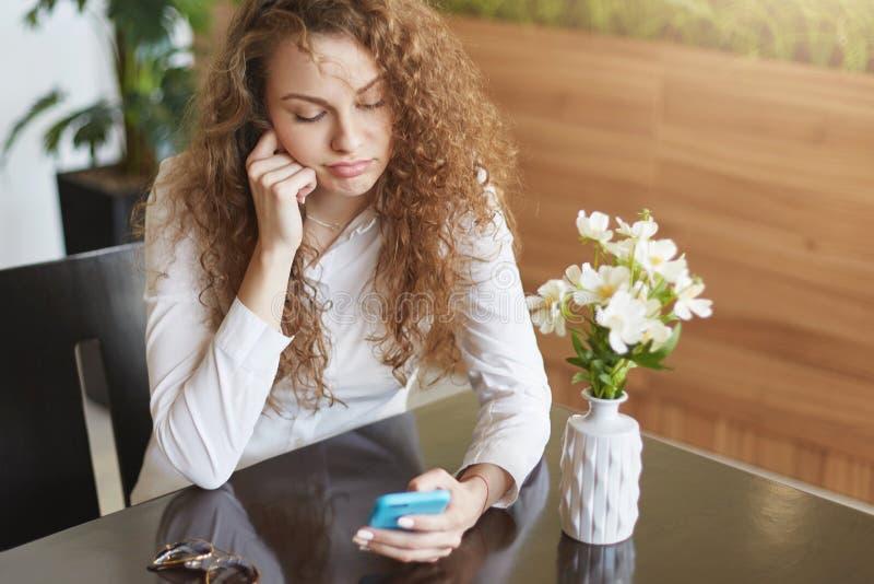La foto della femmina annoiata ritiene stanca come gli aspettare il partner di molto tempo in caffè accogliente, legge le notizie immagine stock libera da diritti