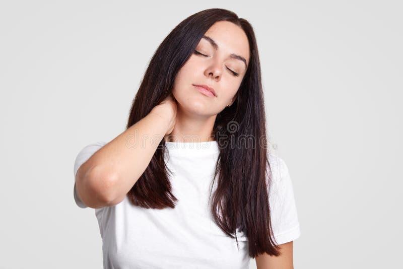 La foto della femmina castana stanca ritiene il dolore in collo come ha stile di vita sedentario, ha bisogno dell'attività fisica immagini stock
