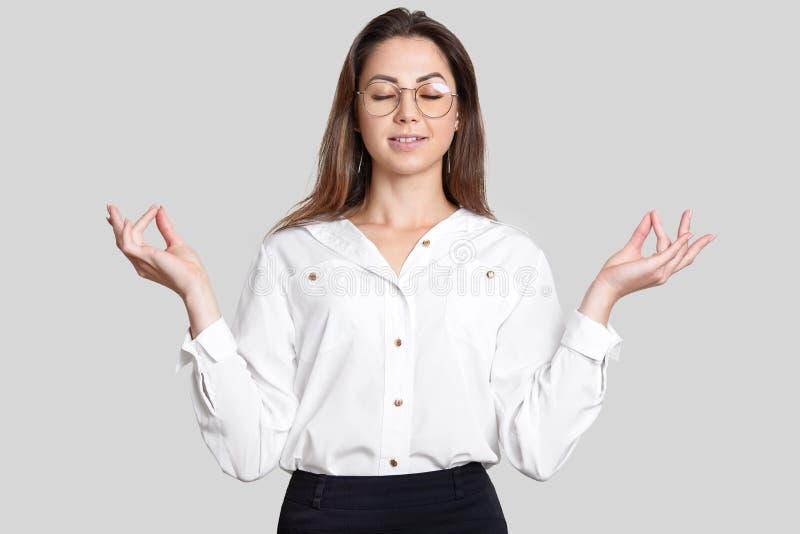La foto della giovane donna calma pacifica si tiene per mano nel gesto di mudra, prova a rilassarsi e concentrarsi prima della ri fotografia stock