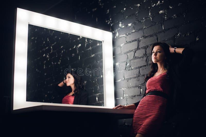 La foto dello studio di modo di bella donna affascinante con capelli castana lunghi indossa il vestito elegante e gli accessori,  immagine stock