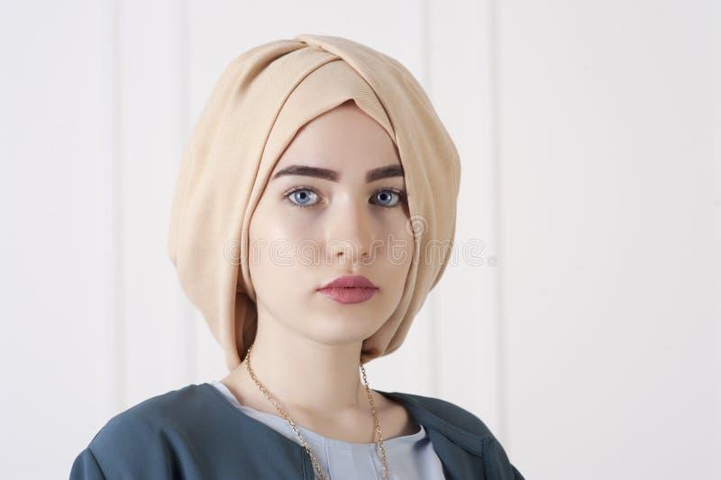 La foto dello studio di una giovane donna orientale scrive dentro i vestiti musulmani moderni ed il bello copricapo a macchina fotografia stock libera da diritti