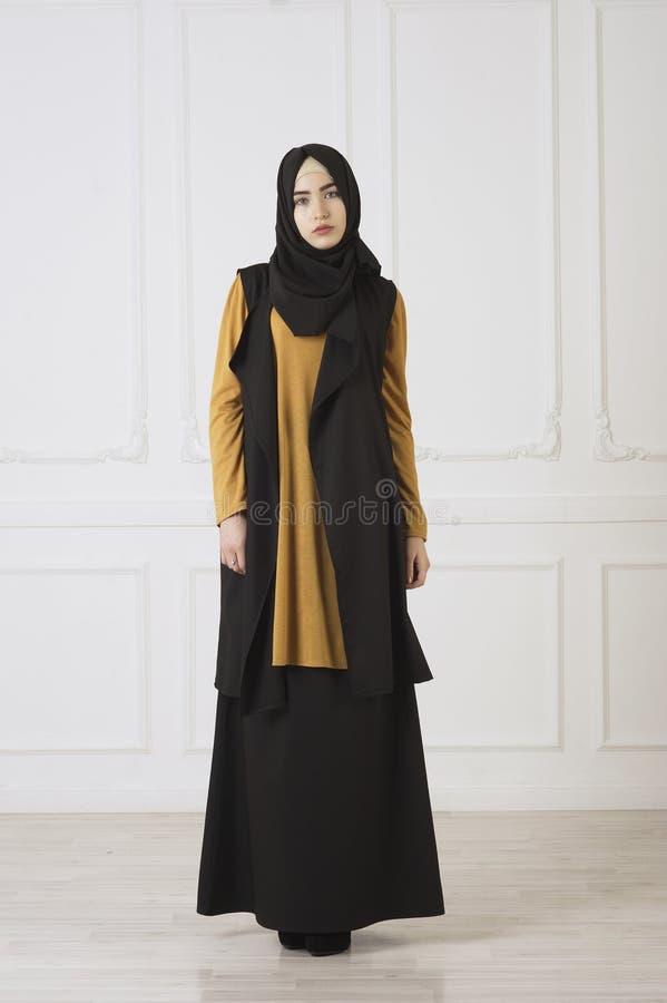 La foto dello studio nei bei sguardi della ragazza della piena crescita nei musulmani orientali veste ed annerisce la sciarpa sul fotografie stock libere da diritti