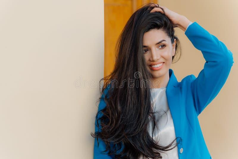 La foto di bella donna castana splendida tiene la mano sulla testa, ha capelli scuri lunghi si è pettinata da un lato, vestito in immagini stock libere da diritti