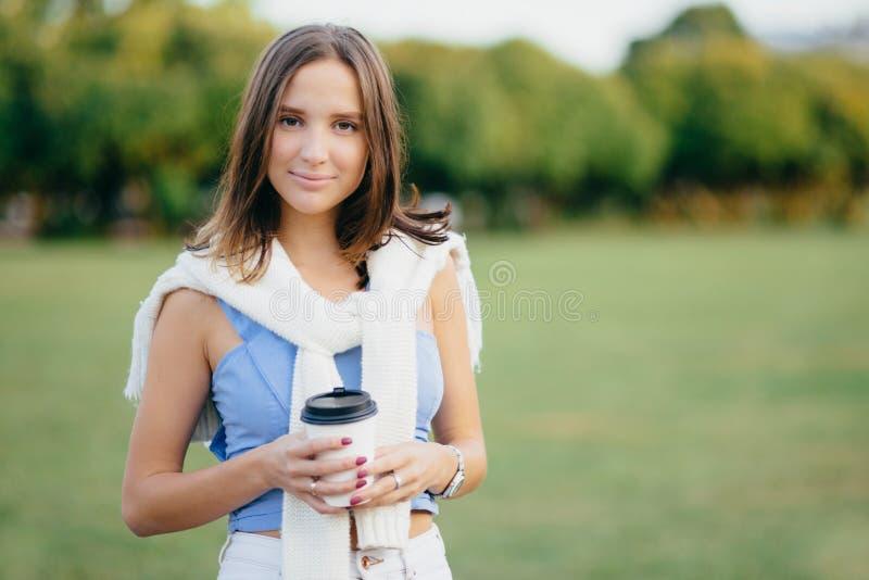 La foto di bella donna con buio ha ballonzolato acconciatura, tiene la tazza di caffè di carta, ha tempo libero, passare il fine  fotografia stock libera da diritti