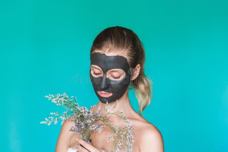 La foto di bellezza di una donna con una maschera nera sul suo fronte sta tenendo i fiori selvaggi asciutti nei precedenti contro fotografia stock libera da diritti