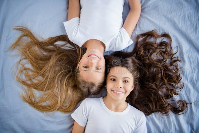 La foto di cui sopra superiore dei bambini attraenti ritiene la camera da letto soddisfatta contenta della stanza del letto di bu fotografie stock
