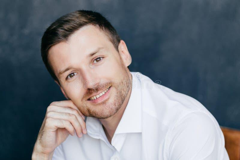 La foto di giovane imprenditore maschio con la setola, tiene la mano sulla guancia, vestita in camicia bianca elegante, pose cont immagine stock