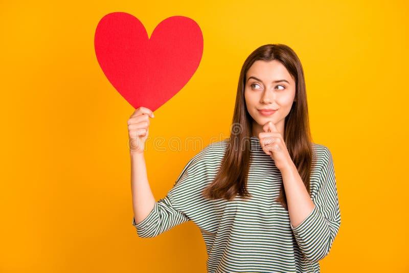 La foto di incantare la donna sospettosa sveglia che pensa sulla che tipo di tre un ha otterrà questo cuore mentre isolata fotografie stock libere da diritti