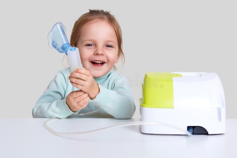 La foto di piccole risate del bambino felicemente, fa l'inalazione, asma delle cure, vestita in maglione blu-chiaro del collo del fotografia stock libera da diritti
