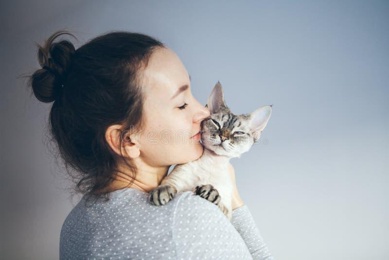 La foto di stile di vita di una femmina vestita casuale sta tenendo e coccole e baciando il gatto sveglio di Devon Rex Il gattino immagine stock libera da diritti
