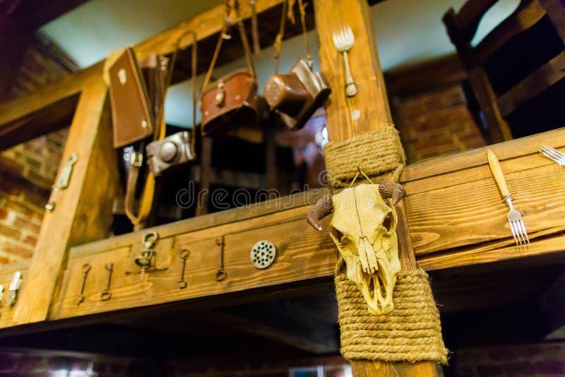 La foto horizontal de la ejecución del cráneo del toro en las escaleras de madera adornadas con llaves, bifurcaciones y bolsas pa fotografía de archivo