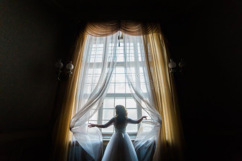 La foto horizontal de la novia que toca las cortinas mientras que se coloca cerca de la ventana fotografía de archivo libre de regalías