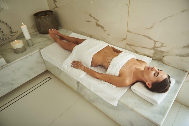 La foto laconica di signora calma che si trova nel bagno turco con i suoi occhi si è chiusa fotografia stock libera da diritti