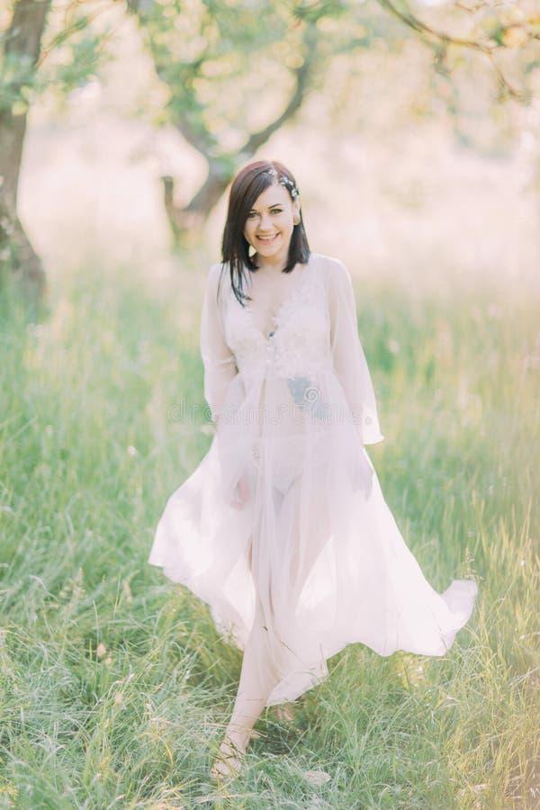 La foto llena-lenght de la mujer sonriente con los tatuajes en su pecho y estómago en el vestido blanco largo que camina en imágenes de archivo libres de regalías