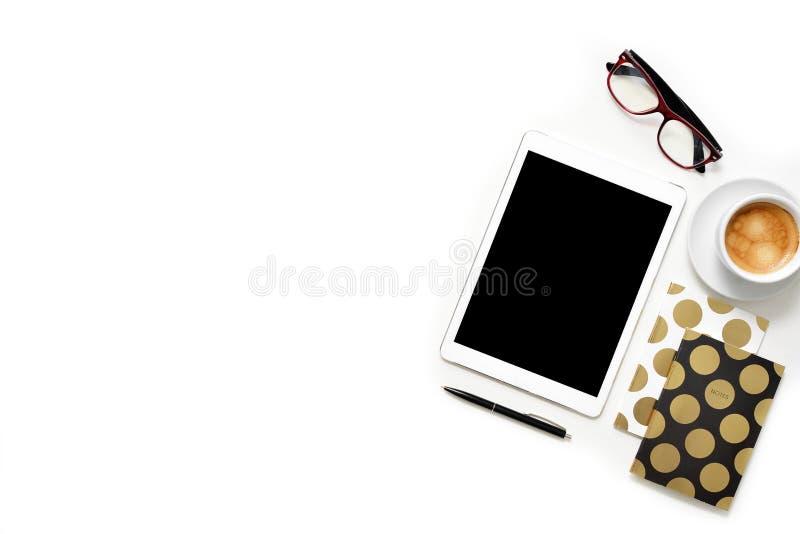 La foto plana de la endecha del escritorio blanco de la oficina con la tableta, la taza de café y el cuaderno del oro copian el f foto de archivo libre de regalías