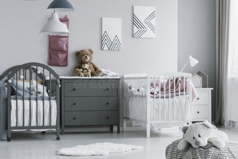 La foto real de un peluche lindo, blanco refiere un taburete en un dormitorio brillante del niño interior con las camas individua fotos de archivo libres de regalías