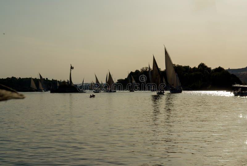 La foto retroiluminada en la puesta del sol del río Nilo cerca de El Cairo con las siluetas de los barcos de navegación típicos d imágenes de archivo libres de regalías