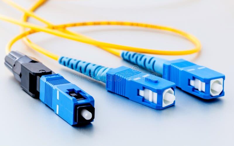 La foto simbólica de los conectores de las fibras ópticas para Internet rápido conecta foto de archivo libre de regalías