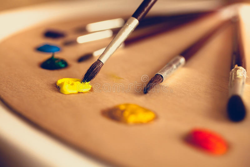 La foto tonificata dei pennelli che si trovano sulla tavolozza ha immerso in pittura ad olio fotografia stock