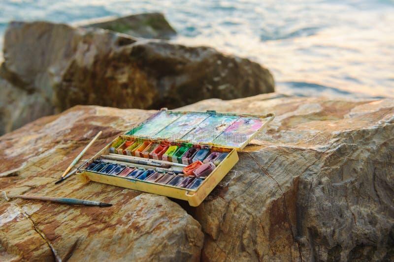 La foto utilizó la caja de pinturas del agua-color, brushon de la pintura, cepillos en piedras cerca de la orilla de mar fotos de archivo